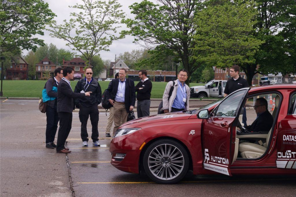 AutoSens Detroit attendees prepare for a self-driving vehicle demonstration as part of the event in May 2018. A track was set up on the campus of Wayne State University where attendees could experience the technology firsthand. Photo: Alex Hartman for Sense Media.