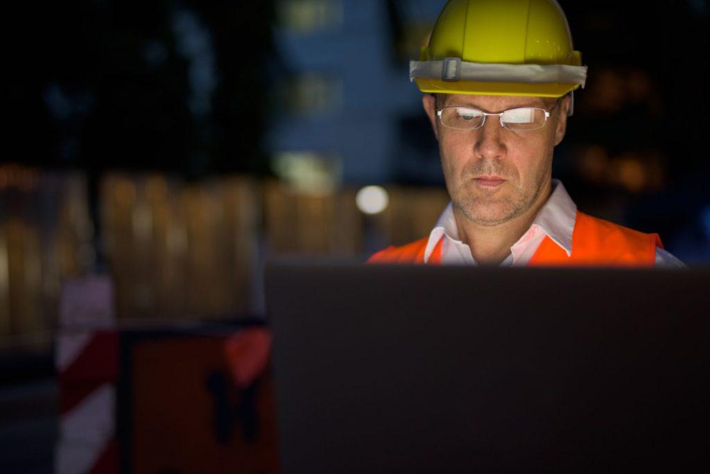 Construction worker looking at a laptop with 6D Road Scanning data.