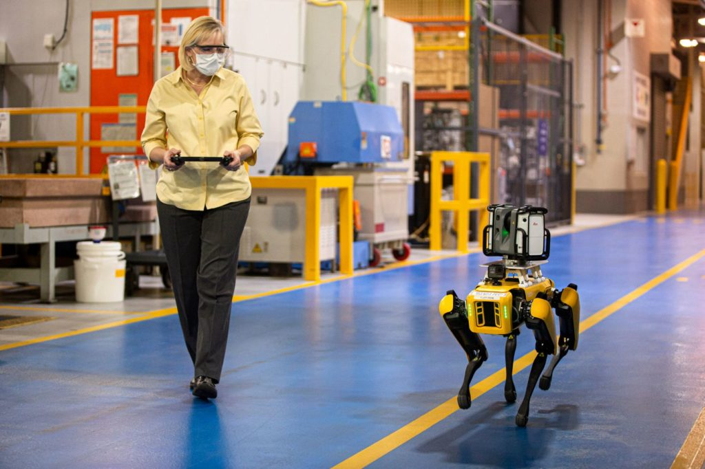 Ford Digital Manufacturing Engineer Paula Wiebelhaus walks with Fluffy. Wiebelhaus controls the robotic pup with the video-game-style tablet in her hands.