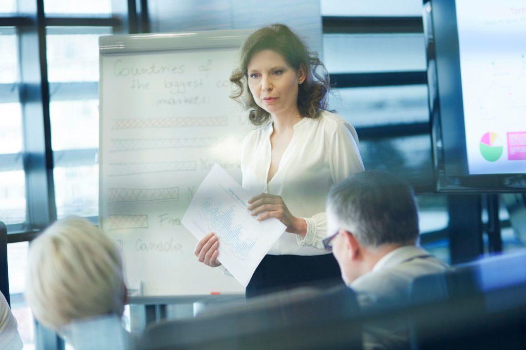 Female presenting in the boardroom.