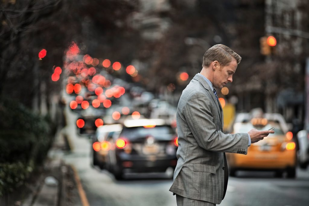 Man looking at his cell phone while cars pass by on the street.