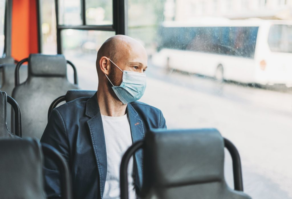 Man riding a bus with a facemask.