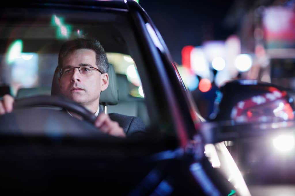 Man driving a car at night.