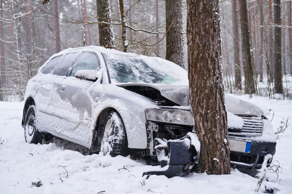 Car crashed into a tree in snowy weather.