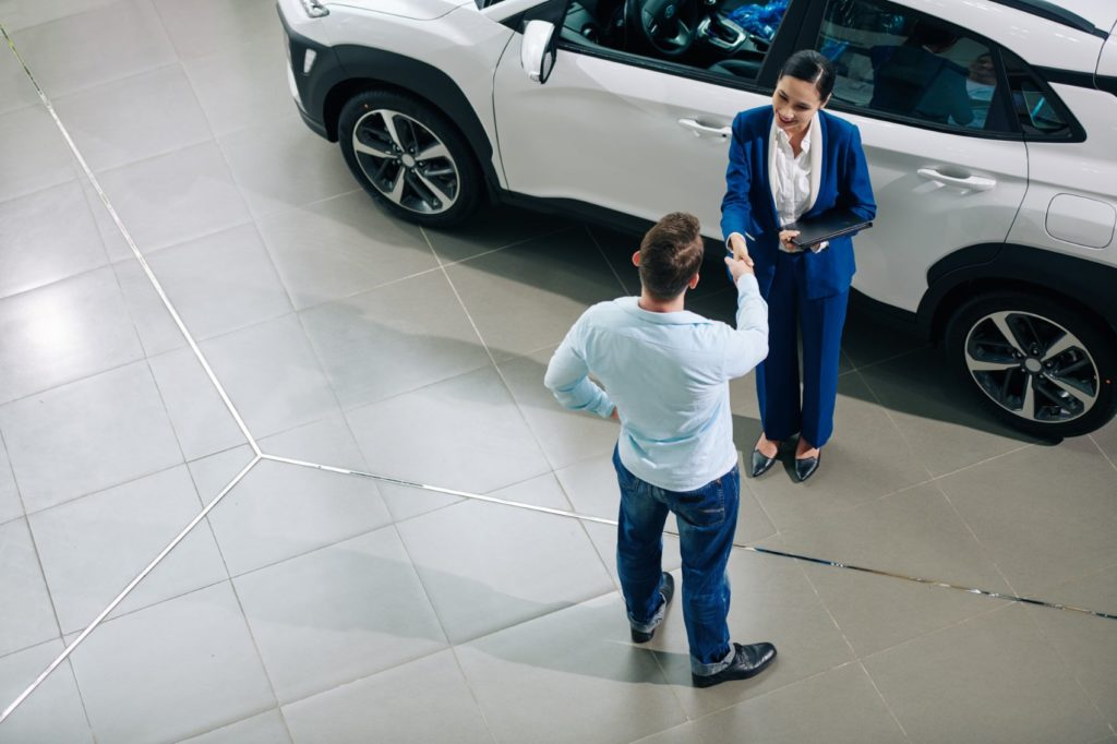 Sales consultant at a dealership with a customer.